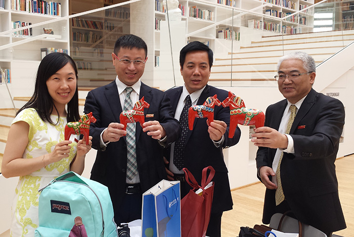 Delegation from China holidin their gifts, Dala Horses, from Dalarna University in the Campus Falun library.