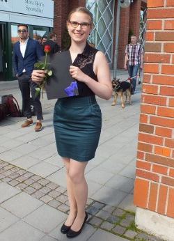 Student standing with a rose in her hand on graduation day