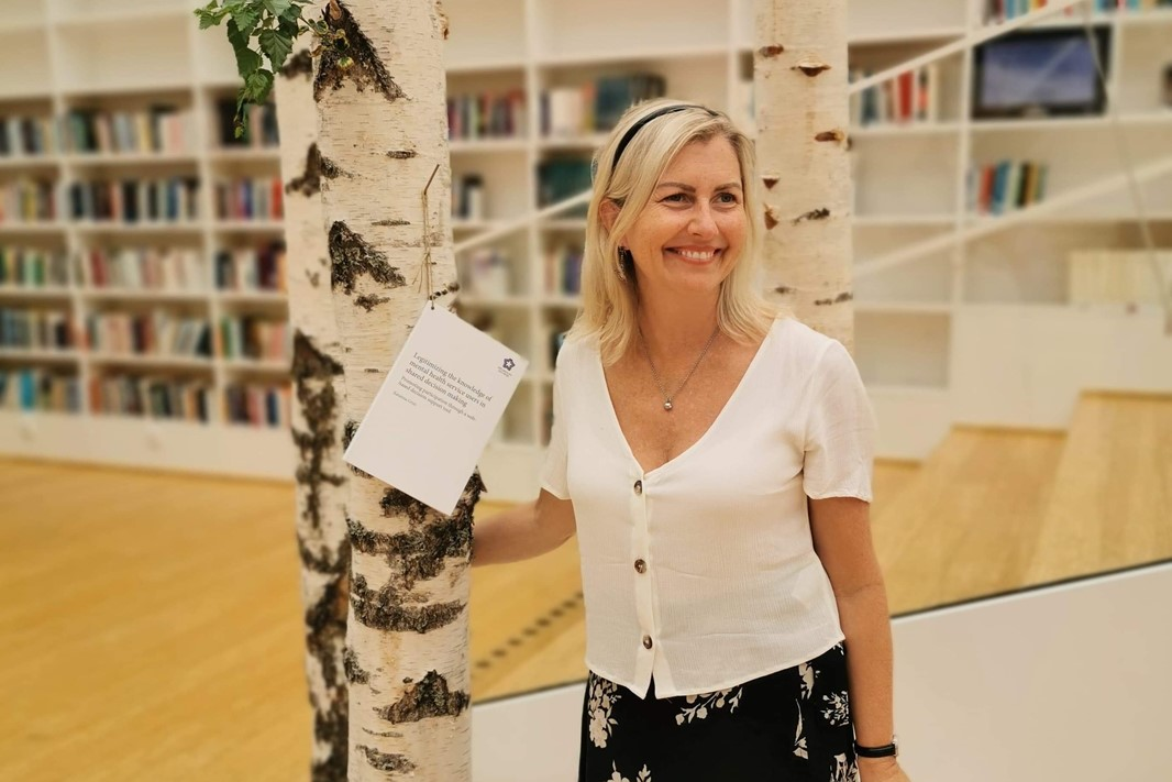 Katarina Grim nails the notification to a piece of a tree in the library at Campus Falunher