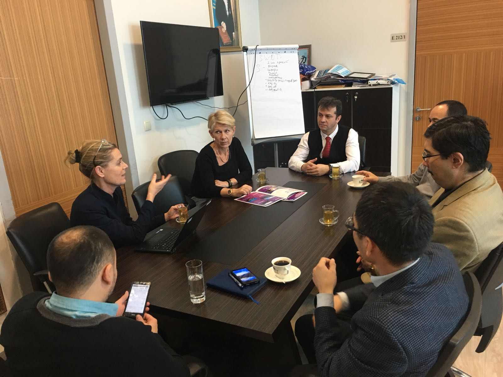 The representatives from Dalarna University and the hosts in Kazakhstan gather around a table for a meeting.