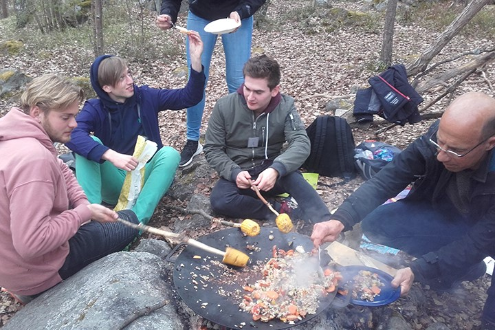 Students sitting outside making dinner over an open fire.